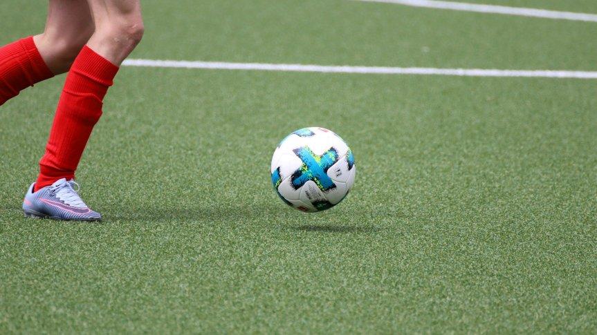 Piłka do piłki nożnej na sztucznej murawie, obok nogi piłkarza.