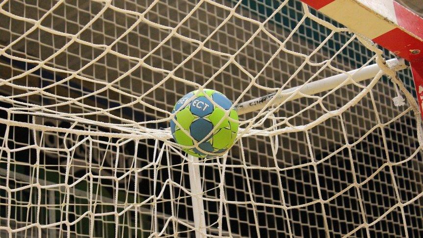 Zielono-niebieska piłka do piłki ręcznej w siatce rozwieszonej na bramce