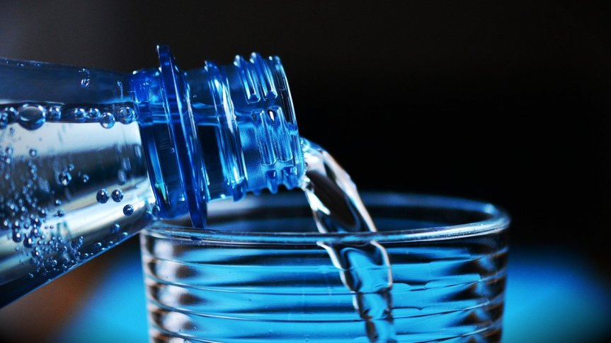 Szklanka, do której nalewana jest woda z plastikowej butelki