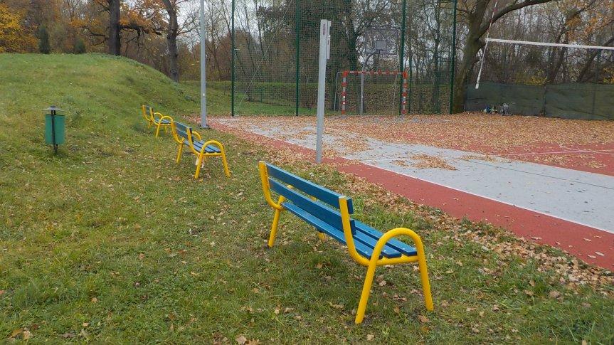Zdjęcie trzech żółto niebieskich ławek znajdujących się przy boisku w Mokrym Dworze
