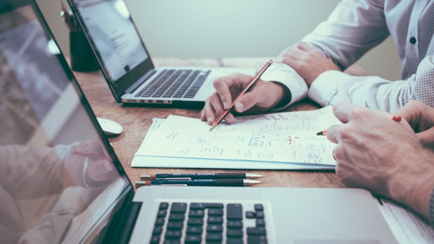 długopis trzymany w męskiej ręce, dwa laptopy